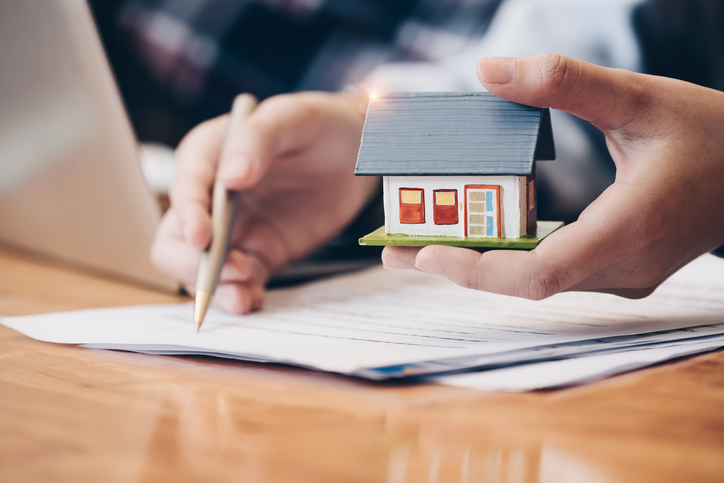 Close up real estate agent with house model hand putting signing contract