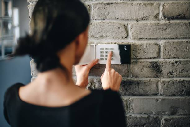 Young woman entering security pin on home alarm keypad. Wired security system with wireless security