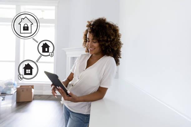 Confident young woman programs automated home security alarm systems with a digital tablet.