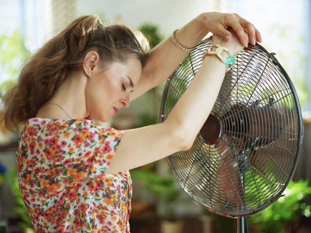 Summer heat. sad middle aged housewife in floral blouse with electric fan at modern home in sunny hot summer day.