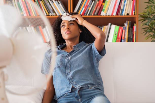 Black woman sweating and trying to refresh at home