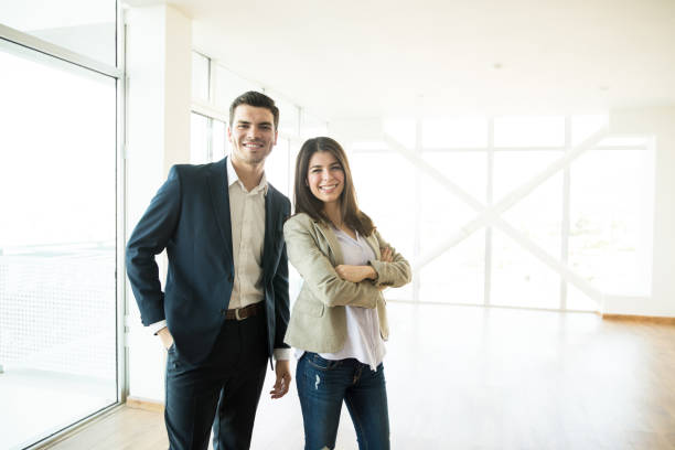 Portrait of smiling male and female real estate agents standing in new apartment