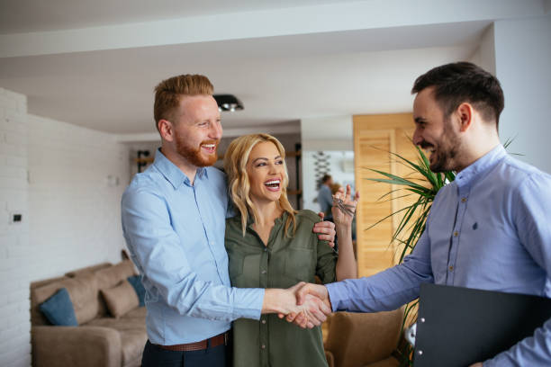 Portrait of financial adviser congratulating to a young couple for buying a new house.